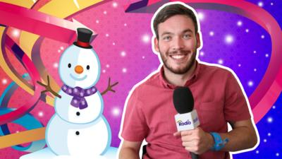 Martin from The Let's Go Radio Club smiling and holding a CBeebies Radio microphone next to a snowman