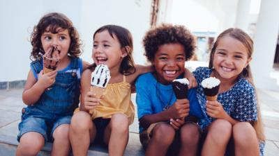 Four young children eating ice cream.