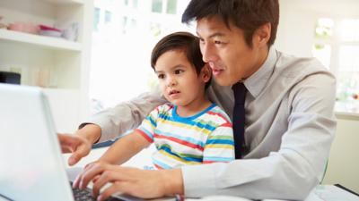 A young boy sat on his father's lap, at a table. The father is typing and showing the little boy the laptop screen.
