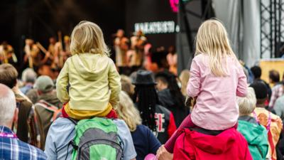 Two young children sat on grownups shoulders. Both are wearing bright colours. They are stood in a crowd watching a performance on a large stage.