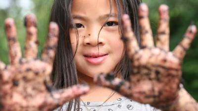 Young girl with her muddy hands held up to camera.