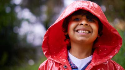 Young boy wearing a red raincoat with his hood up, smiling into camera while it is raining.