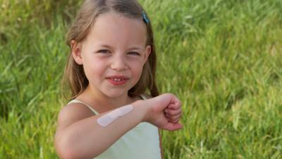 A young girl with her right arm raised in front of her showing that she has a plaster on her arm.