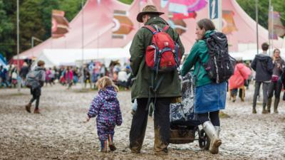 A toddler wearing a rain suit walking next to her father and mother. The mother is pushing a pram as they walk through a very muddy field, with big tents in the background.