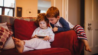 A young girl and boy looking at a smartphone