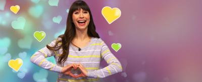 Presenter holding her hand in the shape of a heart with hearts surrounding her