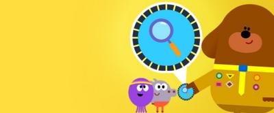 Hey duggee is handing the squirrels a badge. The badge is blue with a magnifying glass on it.