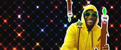 Presenter dressed in a yellow hoodie and sunglasses with his stick friend and sticks surrounding him