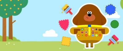 Duggee standing next to lots of badge pieces.