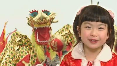 Young girl smiling standing in front of gold Chinese dragon