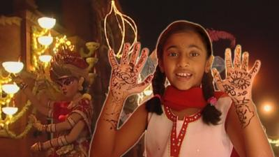 A young girl in traditional Indian clothes in front of Diwali celebrations
