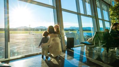 Mother and two children looking out of window at an airport.