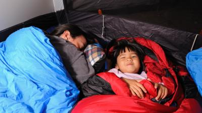 A grownup asleep in a blue sleeping bag who is lay next to a young child, who is lay awake and smiling at the camera, in a red sleeping bag.