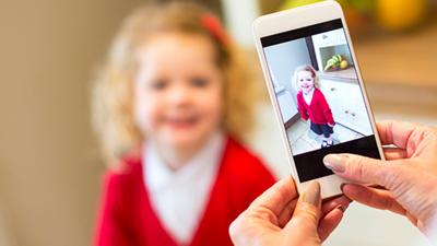 A little girl wearing a plain school uniform having her picture taken with a mobile phone.