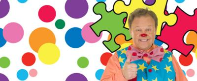 Mr Tumble is smiling with a thumbs up, with jigsaw pieces surrounding him.