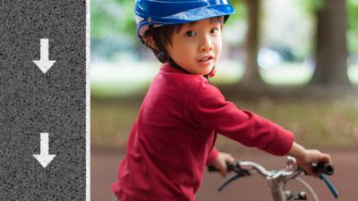 Little boy sat on a bike with his head turned so that he is looking at the camera