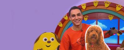 Ben wearing a Waffle sock puppet, next to a cardboard cut out of Waffle the Wonder dog, in the CBeebies House.