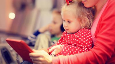 Young child and her mother sat on a plane playing on a tablet.