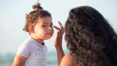 Young girl having suncream applied by her mother.