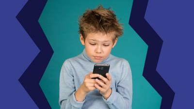 A young boy stares at his phone with blue and purple shades behind him