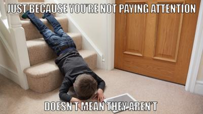 Child lying face down on stairs with iPad next to him.