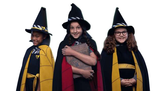 Three young girls are dressed in black cloaks and wearing witches hats (Enid, Mildred