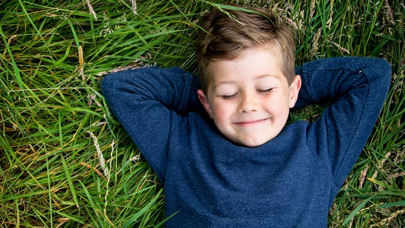 A young boy lying on the grass with his eyes closed looking happy.