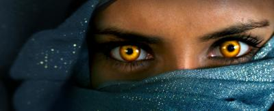 A girl with bright yellow eyes stares with determination with the rest of her face covered by her hijab.