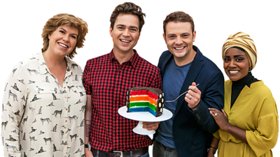 Four people stand in a group holding a chocolate cake with bright colourful layers inside it (Bake Off Judges and Sam and Mark).