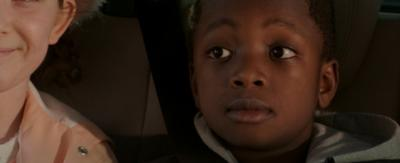 A young boy in the back of a car.