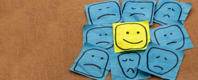 A yellow piece of paper with a smiley face drawn on it, in the middle of blue pieces of paper with sad faces drawn on them.