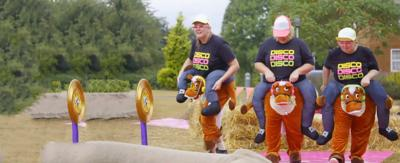 Three woman dressed in costumes that look like they are riding horses, run through an assault course.