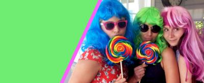 Three women smile posing with brightly coloured wigs and lollipops.
