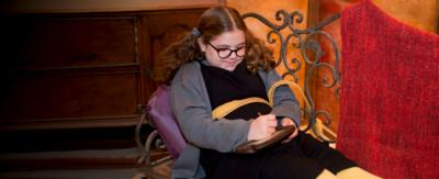 A girl wearing glasses and her hair in bunches, sits on a sofa looking down at a tablet shaped device that's wooden (Maud with her Maglet).