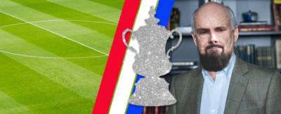 A middle aged man with a bald head and a beard and the FA Cup trophy next to him