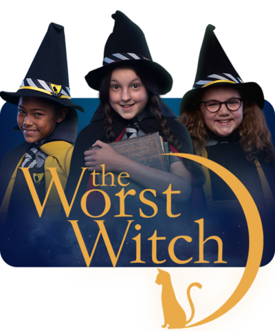 Three young girls are dressed in black cloaks and wearing witches hats (Enid, Mildred and Maud).