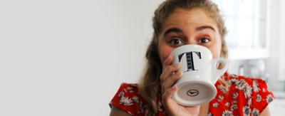 A girl smiles behind a mug with a 'T', she is framed by the words 'Blog Update'.