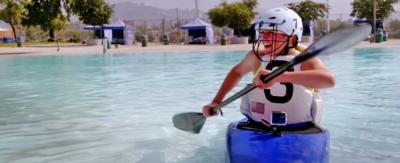 A girl wearing a helmet and paddles a canoe