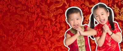 Two smiling children celebrate Chinese New Year