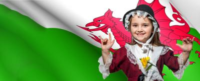 A little girl wearing traditional Welsh clothing, standing in front of the flag of Wales