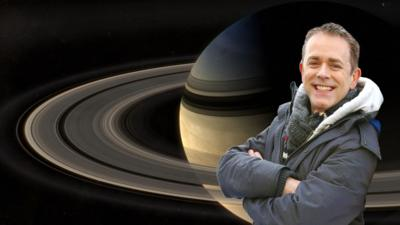 Chris from CBeebies Stargazing in front of the planet Saturn and its rings.