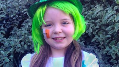 Rachel from My CBeebies Special Day with a green hat and wig on, with an Irish flag painted on her cheek.