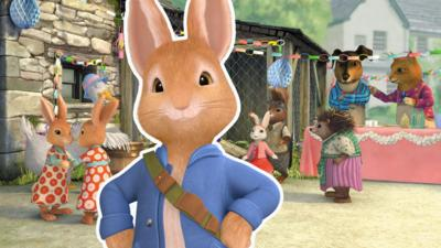 Peter Rabbit standing with his hands on his hips, in front of a spring time party scene.