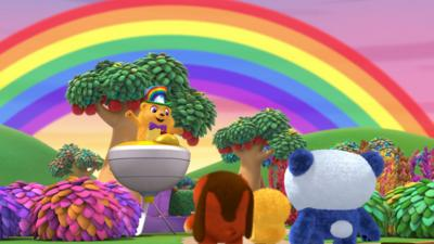 Ruff-Ruff, Tweet and Dave watch Hatty the Hamster on his Spin-Again spinning top craft underneath a large rainbow.
