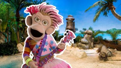 Panzee from ZingZillas playing the bass guitar on a beach.