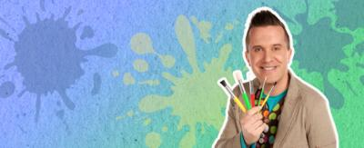 Mister Maker holding up paint brushes.