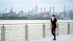 A woman wearing a mask walks through Brooklyn