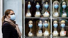 A woman wearing a protective face mask walks past a shop window displaying mannequin heads with masks in Paris, France, 28 October 2020