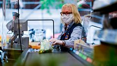 A cashier wearing a mask at Aldi