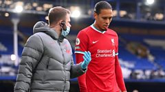 Virgil van Dijk walking off the pitch after suffering a knee injury against Everton